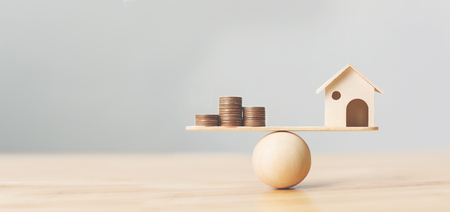 Foto de Wooden home and money coins stack on wood scale. Property investment and house mortgage financial real estate concept - Imagen libre de derechos