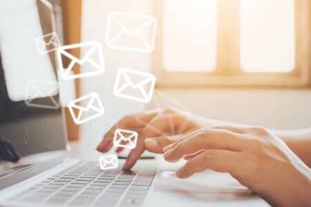 Foto de Email marketing and newsletter concept. Hand of man sending message and laptop with e-mail icon - Imagen libre de derechos