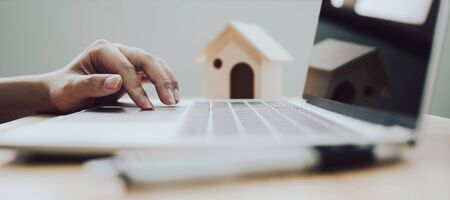 Photo pour Concept of property investment, Mortgage and real estate residental house. Hand using laptop with pen and wooden house - image libre de droit