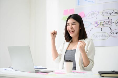 Photo pour Successful business woman working in a workplace. She feels happy and smiles. Computer laptop and paperwork on desk - image libre de droit
