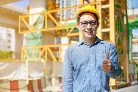 Photo pour New generation of asian engineers are working on the construction site. He looks handsome and smart. - image libre de droit