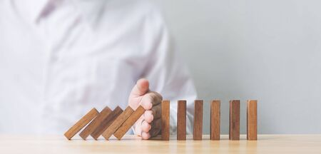 Foto de Hand stopping wooden domino business crisis effect or risk protection concept - Imagen libre de derechos