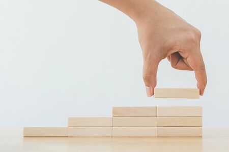 Photo pour Hand arranging wood block stacking as step stair. Ladder career path concept for business growth success process - image libre de droit