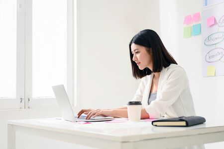 Foto de Concept of work from home. Young asian business woman working on computer laptop in office room with paperwork document on desk - Imagen libre de derechos