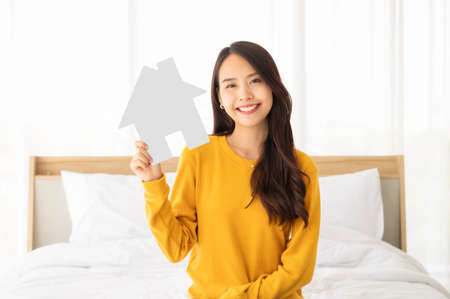 Photo pour Beautiful asian woman happy and smile sitting on bed in bedroom and holding paper house symbol - image libre de droit