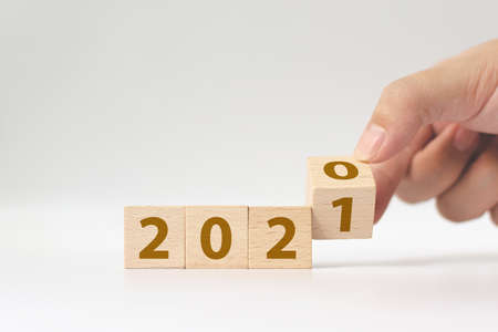 Foto de New year 2020 change to 2021 concept. Hand flip over wood cube block - Imagen libre de derechos