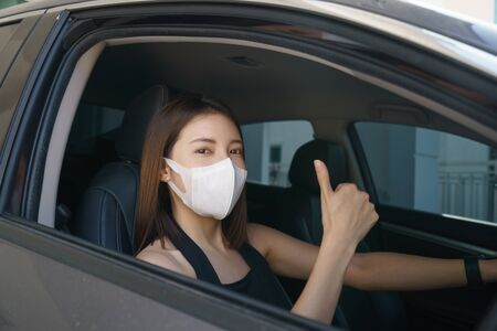 Photo pour Wome wearing surgical mask in the car, for corona virus or Covid-19 protection. - image libre de droit