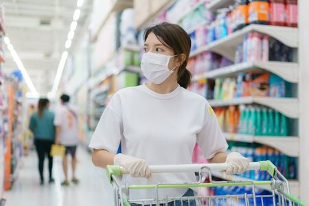 Foto für Woman wearing surgical mask and gloves with a shopping trolley, shopping during a Coronavirus  pandemic. - Lizenzfreies Bild