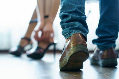 Photo pour Body part : Couple feel romantic . Woman take off  high heels shoes  in bedroom. Sex concept. - image libre de droit