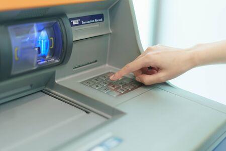 Photo pour Woman finger pressing a button of Automated Teller Machine( ATM ) - image libre de droit