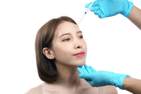 Photo pour Hands of beautician injecting Botulinum Toxin A to asian woman in eye area. - image libre de droit