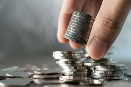 Foto de Hand put coins to stack of coins on white background, Investment and saving concept. - Imagen libre de derechos