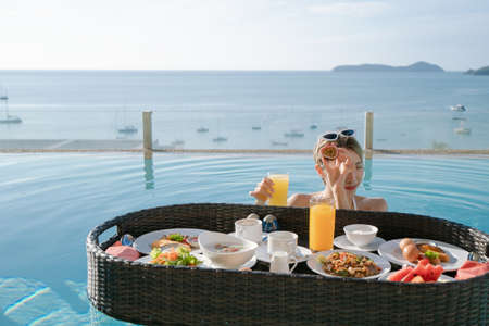 Photo pour Happy woman relax with floating breakfast in swimming pool villa hotel resort. - image libre de droit