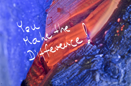 Photo pour Words You make the difference! handwritten on red burn wooden background. - image libre de droit