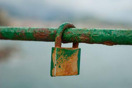 Photo pour Old padlock, a sign of love, attached to a marine railing, worn by salt - image libre de droit