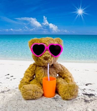 Photo for teddy bear sunbathing on a tropical beach and drinking - Royalty Free Image