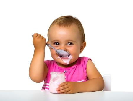 girl eating yogurt isolated on white