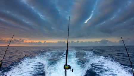 Photo for Boat fishing rods over a beautiful cloudy seascape - Royalty Free Image