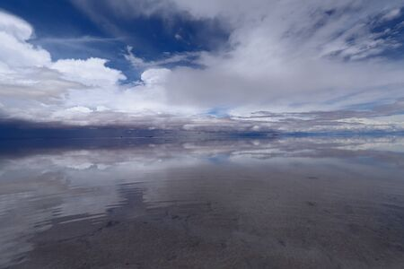 Photo for The Salar de Uyuni flooded after the rains, Bolivia. Clouds reflected in the water of the Salar de Uyuni, Bolivia - Royalty Free Image