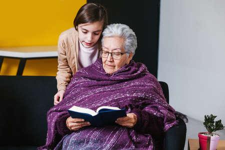 Foto de Latin granddaughter and mexican grandmother reading a book and tablet in Mexico city - Imagen libre de derechos