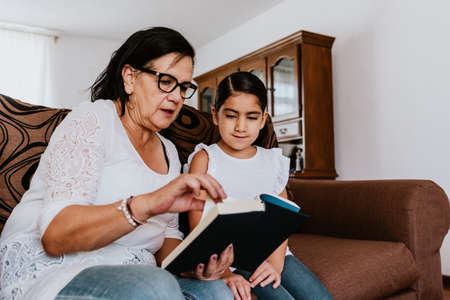 Foto de latin grandmother with granddaughter sitting on couch at home and reading book in Mexico city - Imagen libre de derechos