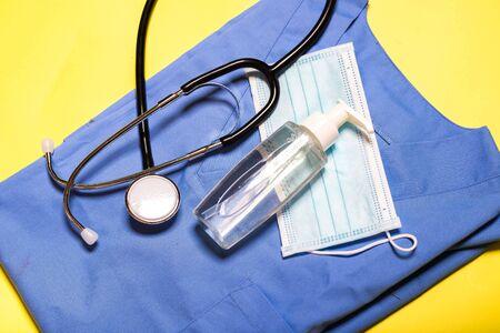 Photo pour stethoscope with a mask and a hand dispenser on a blue medical uniform - image libre de droit