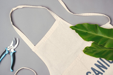 Apron with leaves and scissors on table. Top view.