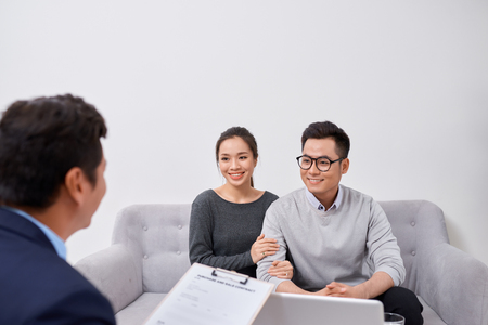Photo pour Happy young couple hold each otherâ??s hands listening to female agent, planning wedding, consulting investment advisor, hearing good news, casual marriage registration, buying real estate - image libre de droit