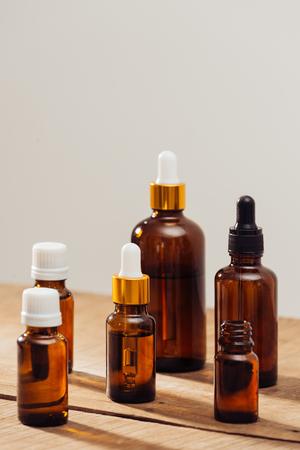 Photo pour Essential oils bottles on wooden desk with candlelight beside. Spa wellness set. - image libre de droit