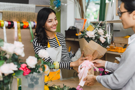 Photo for Ho Chi Minh City, Vietnam - 21 August, 2017: happy smiling florist woman making bouquet for and man or customer at flower shop - Royalty Free Image