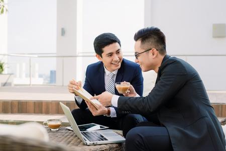 Photo pour two asian business executives using ipad in city park. - image libre de droit