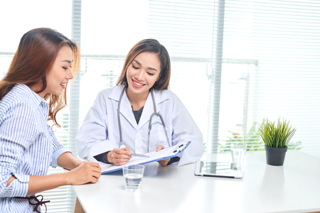 Photo pour Female doctor talks to female patient in hospital office while writing on the patients health record on the table. Healthcare and medical service. - image libre de droit