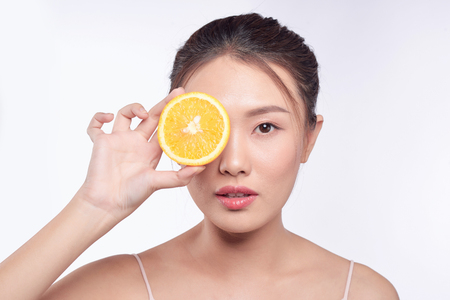 Photo pour young and beautiful asian woman posing with a slice of orange on white background - image libre de droit