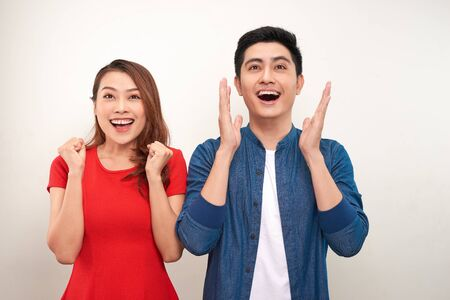 Photo for Young asian couple in love over isolated background celebrating surprised and amazed for success with arms raised and open eyes - Royalty Free Image