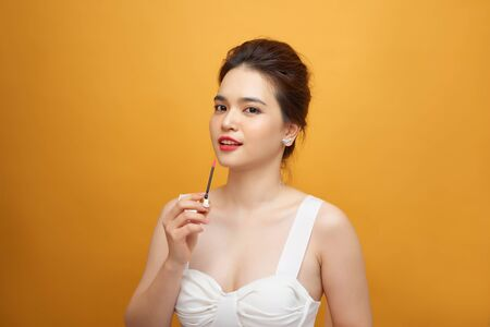 Photo for Perfect girl holding lipstick on yellow background, close up portrait. - Royalty Free Image