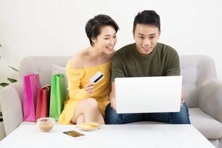 Foto de Young Asian Couple Making Online Purchases On Laptop At Home - Imagen libre de derechos