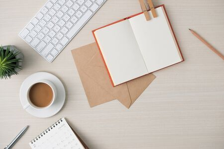 Photo for Modern minimalistic work place. Keyboard, notebook, envelope, glasses, pen, pencil, coffee on wood table. Top view with copy space, flat lay - Royalty Free Image