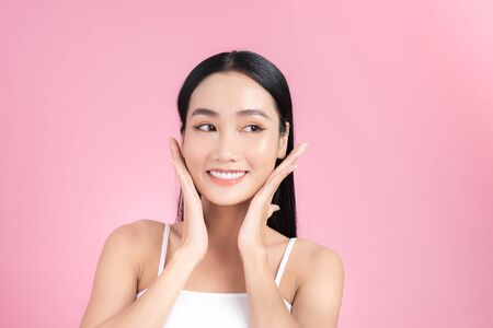 Photo pour Beautiful young Asian girl touching her perfect skin on pink background. Skin care concept - image libre de droit