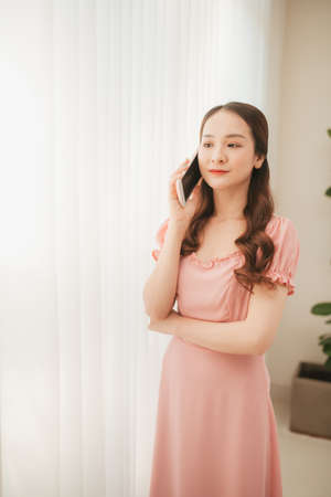 Photo for Beautiful young asian woman calling and talking with family by using mobile phone - Royalty Free Image