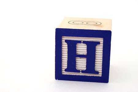letter h in a alphabet wood block on a white surface