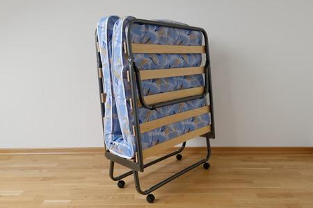 Photo pour A folding bed in front of a white wall an a blue mattress - image libre de droit