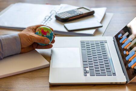 Photo pour A businessman plays with a stress ball while he investigates the market - image libre de droit
