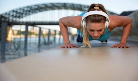 Foto für Early in the morning, after sunrise, in the city by the river, a young attractive woman does fitness workouts on the promenade and listens to music over headphones - Lizenzfreies Bild