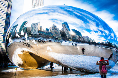 Skygate Bean covering by snow against high building towers and blue sky with unidentified visitors at Millenium Park