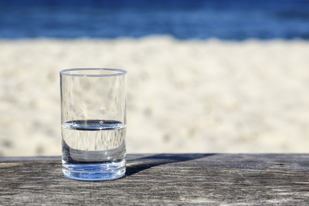 Photo pour Glass of water which is half-full stands on a wooden table which stands on the sand beach by the sea - image libre de droit