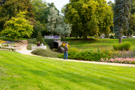 Marianske Lazne, Czechia - September 09, 2017: Several people take advantage of the beauty of a park designed in the city, bringing inhabitants and tourists closer to communicating with nature.