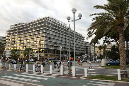 Nice, France - September 24, 2018: The large building of the famous Le Meridien hotel is seen at the Promenade des Anglais. The evening light colors one of the facades of the building.