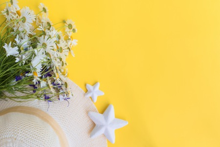 Summer hat and flowers on a yellow background. Top view, flat lay