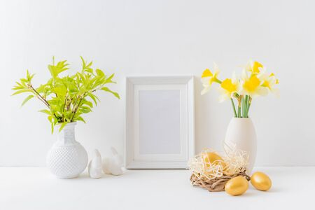 Photo pour Home interior with easter decor. Mockup with a white frame and yellow daffodils in a vase on a light background - image libre de droit