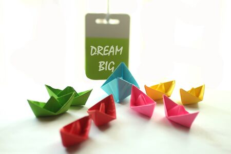 Photo for Motivational quote- Dream Big. With colorful paper boats and a motivation note hanging on the wall for the team. Teamwork, leadership and togetherness concept in white background. - Royalty Free Image